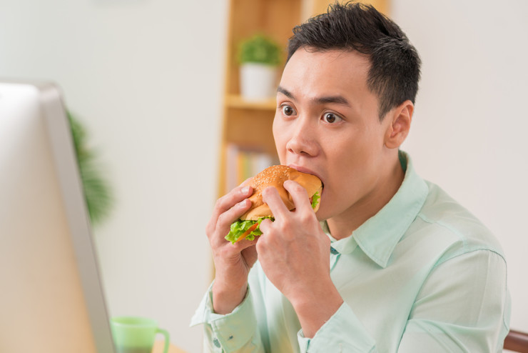Man eating hamburger at stressful work at office ** Note: Shallow depth of field